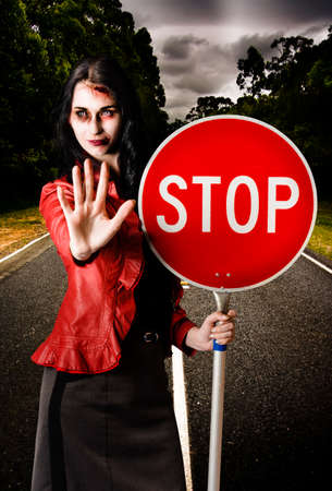 dreary: Zombie businesswoman halting traffic on a dreary road while holding a stop sign in a dead end concept