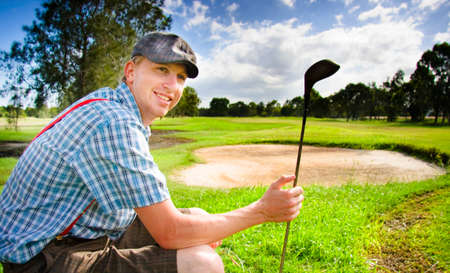 yard stick: Professional Golf Player Smiles In Cap Suspenders And Check Shirt While Sitting Near A Sand Bunker And Golfing Fairway In A Happy Outdoor Summer Sports Portrait
