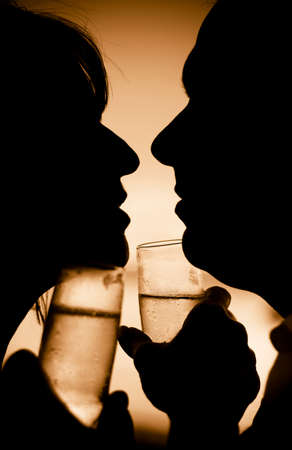 steamy: The Sunset Silhouettes Of A Intimate Couple Moving Closer To Embrace In A Desire Filled Beach Kiss Is Captured In Summer Love
