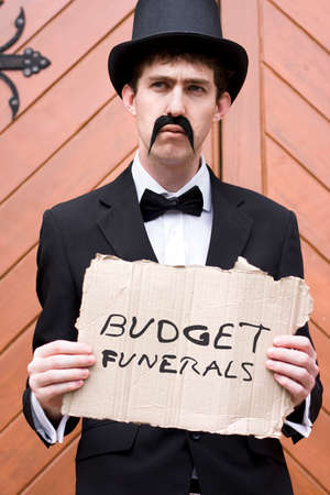 mortician: Selling Death A Funeral Salesman Offers Cheap Burials While Holding A Budget Funerals Sign
