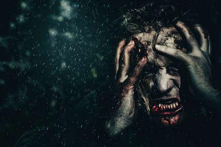 demon: hombre zombie mal que expresa miedo al girar en el bosque muerto en vida en la oscuridad perseguido. agarrando el terror Foto de archivo