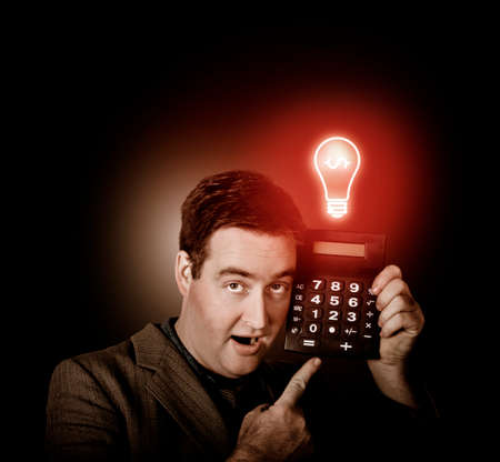 save electricity: Financial business man with shocked expression pointing to calculator with switched on red light bulb. Money idea Stock Photo