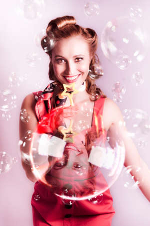 vouge: Selenium Artistic Portrait Of A Beautiful Pinup Model Wearing Scarf And Red Rockabilly Dress Blowing Soap Bubbles At A Retro Nightclub Party Stock Photo