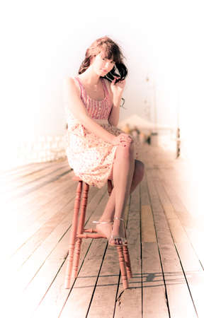 fading: Overexposed Vintage Lifestyle Portrait Of A Young Woman Resting A On Stool Outdoors On A Old Wooden Pier With Background Fading To White Stock Photo