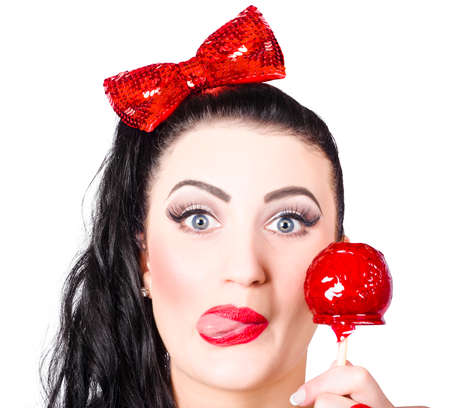 Funny closeup portrait on the face of a sweet pin-up girl eating a candy toffee apple with a cheeky expression over white background Imagens