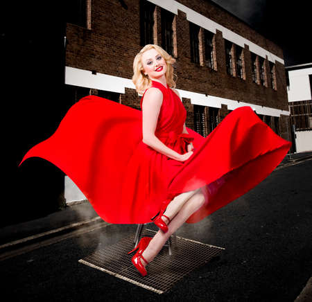 red dress: Blond pinup girl doing a sexy red dress dance underneath an open street vent. Classical fashion styles. Stock Photo