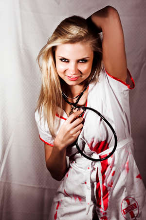 pervert: Psychotic Killer Nurse. A nurse in a bloodstained uniform and stethoscope glares menacingly at the camera in a horror and killing concept Stock Photo