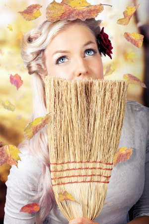 pointless: Cute Pin Up Girl In Retro Style Portrait Holding Old Broom While Cleaning Up Falling Leaves From The Front Yard And Back Garden In A Representation Of Spring Cleaning Stock Photo