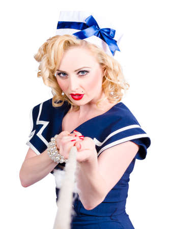 grit: Strong blond sailor pin-up model pulling on tug of war rope in a show of grit and determination over white background
