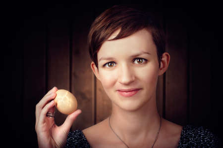 fissure: Attractive young brunette woman with short hair standing in kitchen holding hatching egg. New Beginning