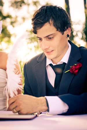 contentedness: Young Handsome Groom Signing A Marriage Contract Using A Feather Quill With An Expression Of Happiness And Contentedness With A Sunlit Background