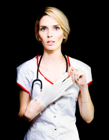 rectum: Serious young nurse with short blonde hair removing her latex gloves after doing blood work on a patient