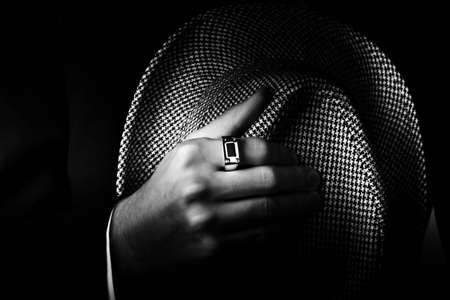 dapper: Classic black and white close-up photograph of a male hand wearing premium ring and holding a stylish hat Stock Photo