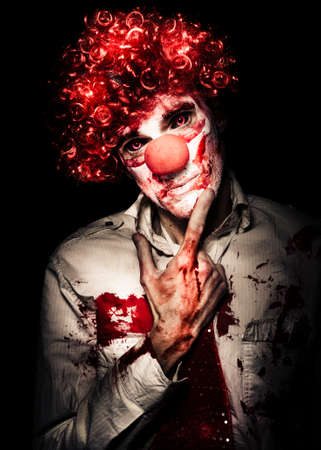 horror: Sinister Bloodstained Clown In A Curly Red Wig Standing Pensively Contemplating His Next Murder Victim With A Dispassionate Look, Halloween Horror Concept Stock Photo