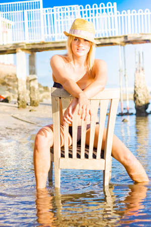 blonde haired: Young Attractive Blonde Female Sitting In Antique Wooden Chair In Shallow Ocean Water With Smiling And Relaxed Expression As If She Has No Worries
