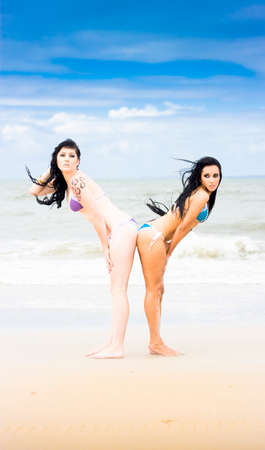 bent over: Touching Relationship Portrait Of Two Female Best Friends In A Bum To Bum Beach Connection Or Bond Stock Photo