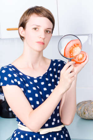 antioxidants: Woman closely examining the healthy properties inside a sliced tomato with magnifying glass