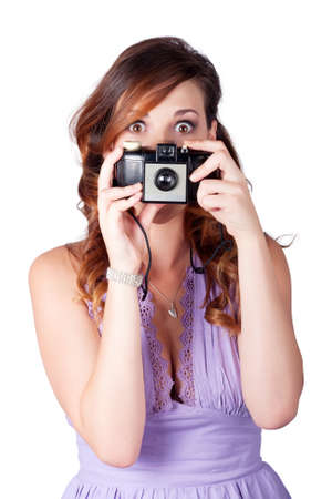focuses: Young wide-eyed caucasian woman taking picture with vintage camera over white background