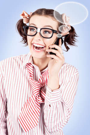 dweeb: Laughing humourous young female student with pigtails and geeky eyewear on a mobile call with blank speech bubbles floating out of the handset for your text