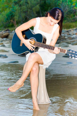 woman guitar: Woman Holding And Strumming Guitar While Sitting On A Water Pillar At A Beach Location In A Relaxation Pastime Picture Stock Photo