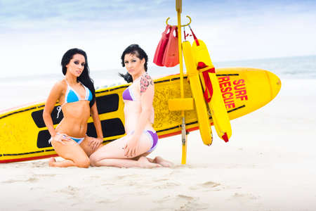 rescue: Sexy Lifesaver Beach Patrol Concept With Two Glamour Beach Models Pose By A Surf Rescue Lifeguard Surfboard