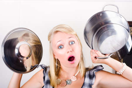 dismayed: Young open-mouthed blond woman holding empty pot and lid with surprise expression
