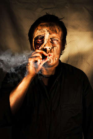 puffing: Decaying zombie smoking a cigarette in a conceptual image of what can happen to someone who cannot kick the habit