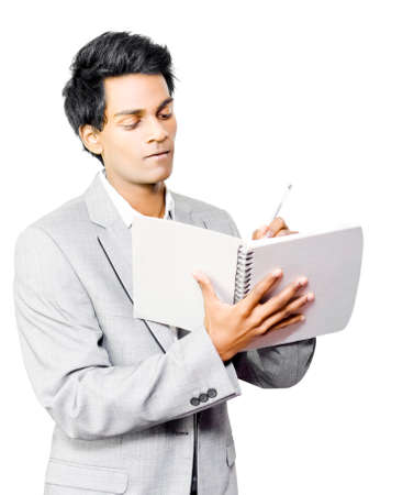 taking inventory: Young Asian businessman taking notes in a wirebound notebook as he attends a business presentation or as he conducts an inspection and inventory