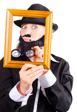 critic: A woman in fake beard and mens clothes looking through an empty picture frame. Art critic concept