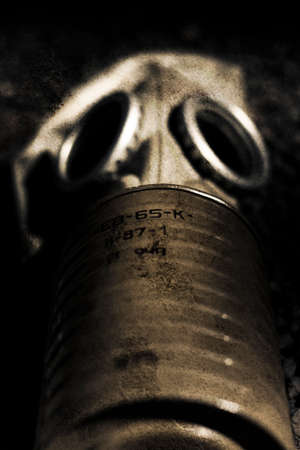 gasmask: Creepy And Eerie Photo With Texture Of A Military Gasmask Laying On A Battlefield In A Horrors Of War Conceptual Stock Photo