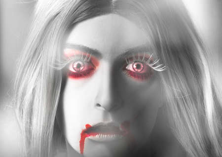 bloodshot: Spooky close up portrait on the face of a beautiful blond vampire girl looking out with a frightening expression of shock horror with bloodshot red eyes and bloody mouth