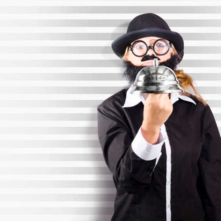 summon: Square portrait of a comic business man holding large customer service bell on striped background Stock Photo