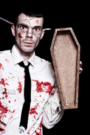 standing up: Halloween Businessman Covered In Blood Holding Open Funeral Casket On Black Background