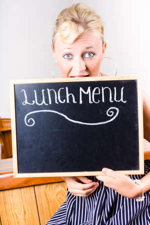 nibbling: Funny portrait of a peckish woman nibbling on a lunch menu in a depiction of hunger Stock Photo