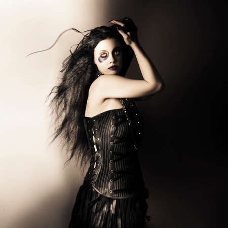 Dark studio portrait of a sexy fashion model  with dark wavy brunette hair wearing black corset and jester make up