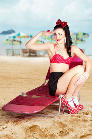 recliner: Sexy beach pin up girl wearing polka dot swimwear with matching high heels sitting on a retro pink recliner chair Stock Photo