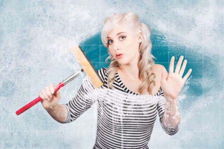 tidying up: Creative pinup portrait of an attractive young housewife cleaning glass shower door with white soap suds and squeegee. Clean copyspace Stock Photo