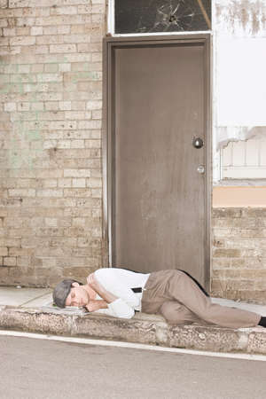 kerb: A Newly Evicted Homeless Man Sleeps On The Kerbside: A Victim Of The 1930's Great Depression