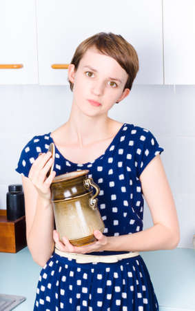 whether: Young woman in kitchen wondering whether to use sugar in jar, healthy eating concept.