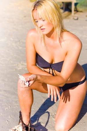 mujer arrodillada: Mujer atractiva del pelo rubio de rodillas en la arena con una concha de mar por la costa de la orilla cuando en una vacaciones de turismo Para explorar la naturaleza, Foto de archivo