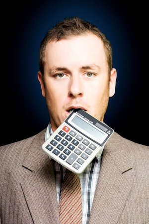 credit crunch: Dazed tired accountant dangles a calculator out of his mouth after crunching endless numbers to find a solution to debt and improve cash flow liquidity in a credit crunch or financial struggle concept