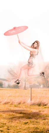blown away: Sky Dance Sees Gustily Winds Send A Parasol Holding Woman Off Into A Skybound Dance While Hovering Flying And Moving Over A Vintage Summer Field Stock Photo