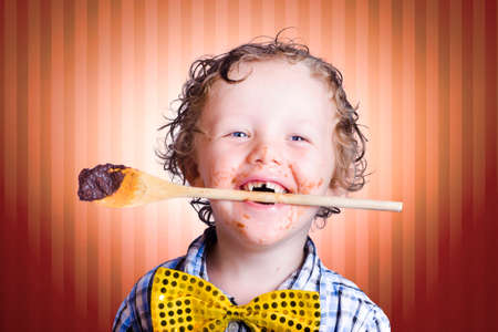 smeared: Adorable Little Boy With Wooden Cooking Spoon In Mouth And Choc Smeared Face Baking Chocolate Easter Cake