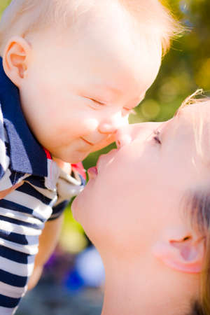 aloft: Joyful young baby with a big grin rubbing noses with Mom as he is held aloft prior to being kissed by her