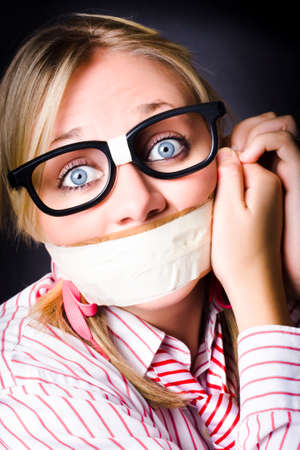 gagged: Young caucasian girl wearing nerdy eyeware with frightened expression attempting to remove tape across mouth in a freedom of information concept