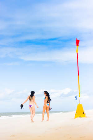 babes: Beach Babes Is Two Distant Bikini Clad Girls Walking Or Strolling Along A Summer Beach In A Playful Friends Concept. Blue Sky With Copy Space Or Room For Text
