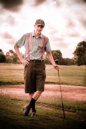 olden day: Happy Old Fashioned Golfer Leans On His Vintage Golf Stick In Front Of A Sand Bunker On A Golfing Fairway In An Olden Day Portait