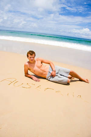 written: Loud And Proud Aussie Sits Next To His Hand Written Trademark In The Sand