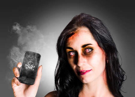 ghoulish: Zombie business girl with bloodshot eyes holding smoking mobile phone with skull and crossbones in a depiction of dead technology