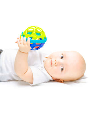 boy kid: Young baby lying contentedly on its back playing with an educational toy designed to teach recognition of different shapes